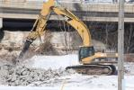 A Cat 330D hammers away during demolition of the existing bridge.