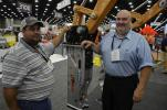 Jonathan Phillips (R) of Gorilla Hammers shows this machine to Robert Mitchell of Dunk Energy, Terre Haute, Ind.