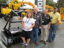 At Bandit Industries' outdoor display, (L-R) are Colleen Hall, Gene Bridges, Ed Woods and Scott Woods. They dodged the raindrops to speak with attendees about the company's 72FM skid steer mulcher head and other land clearing and material proc