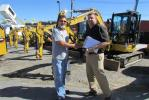 Chris Redding (R), Alban CAT, welcomes his customer Philip Thompson, Dirt Express, Glen Burnie, Md., to the CAT-A-Thon sale.