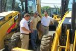 Charlie Silvestri (C) of Tricks LLC., Denville, N.J., is checking out this used Caterpillar 416F with Pat Togno (L) and Dan Scaramella, both of Foley CAT.