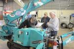 Steve Brown (L) demonstrates the controls on the Maeda spider crane while customers look on.