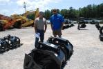 Jeff White (L) and Damian McKay, White's Crossing Trucking, Wiggins, Miss., inspect skid steer attachments.