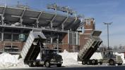 Barbara Haddock Taylor/Baltimore Sun photo Workers dump snow in the parking lot at M & T Bank stadium. States not affected by the storm have sent crews to help with cleanup.
