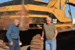 Frank Campbell (L) and Art Martori take a break from the action in front of an older model Caterpillar excavator.  Campbell owns B&J Metals & Materials of Eloy, Ariz., and Martori operates Martori Farms, which has locations throughout Arizona.