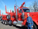 Dick Murphy, equipment sales of General Trailer Company, Springfield, Ore., poses with this Peterbilt truck and logging trailer combo. General supplied this trailer owned by Joel and Daren Olson of Olson Trucking, Vancouver, Wash.