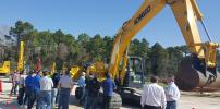 A group of dealer sales professionals gather around KOBELCO's new Generation 10 SK210 excavator to learn the benefits of its innovative features and technologies.