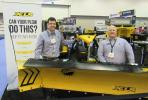 Tyler Jones (L) and Norm Klimko stand ready to answer questions about the many snow and ice control products in the Fisher Plows booth, including this XLS snowplow.