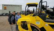 Brad Baum (L) of Stephenson Equipment speaks with Jeff Esbin of J.D. Eckman about the intelligent compaction built into the larger Bomag rollers.