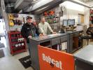 (L-R): Rick Zebro (L) of Zebro Construction, Ham Lake, Minn., and Mike Tangeman, sales, Lano of Anoka, look at parts and attachments.