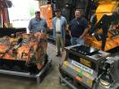 (L-R): Novey Christopher, Jerry Koone and Brian Holland, all of Koone's Well & Pump Services, look over the FAE Advanced Shredding Technologies products hydraulic driven heads, hydraulic mulching heads for excavators, skid steer loaders, backhoes and prime movers.