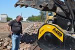 Jerry Buesing of Buesing Corp. inspects the MB America crusher bucket attachment.