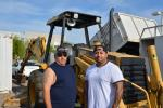 Bill Badilla (L) and Miguel Sanchez, both of Phoenix, Ariz., were interested in this Cat backhoe loader.