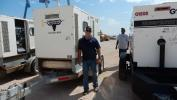 Gary Coburn, G & M Enterprises, Homer, La., inspects a 2011 Sullair NPS-P-150 portable generator during the auction.