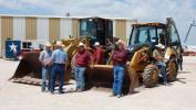 Customers patiently wait for the loader backhoes to be auctioned off.