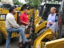 Matt Chin (C) of Foley CAT discusses Caterpillar skid steers with Gus Ramirez (L) and Steve Gattoni, both of Schnell Contracting, Freehold, N.J.
