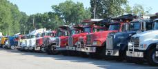 A row of dump trucks awaits their turn on the auction block.