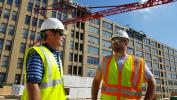 Darin D'Ascanio (L) of Stephenson Equipment and Dan Petrucelli of Lenick Construction discuss the delivery logistics and set up of the Potain T85A on the Hanover at North Broad Project job site.