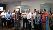 Robert Mann (front holding scissors), DEUTZ Corporation president and CEO and Michael Wellenzohn (back holding scissors), a member of the DEUTZ AG board of management with responsibility for sales, service and marketing, cut the ribbon at the event.