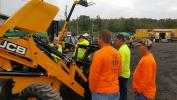 JCB representative Bob Fuend talks with crews from Springbrook Township about the easy accessibility for maintenance on the JCB 3CX backhoe.