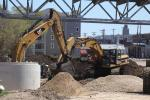 A pair of Cat excavators dig together in a two block area of the city where 29 residential and commercial properties were relocated to make room for the street geometrics of the new bridge.