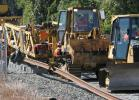 While pulled along the rail bed by a bulldozer, the TCM uniformly lays the ties onto the ballast at predetermined spacing and simultaneously threads the rails onto the ties. (Connecticut Department of Transportation photo)