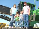 (L-R):?Chasity, Weston, Brayden and Donavon Windham, independent contractor, based in Bay Springs, Miss., look over the forestry equipment, including this John Deere 437D knuckleboom log loader.