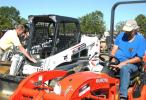 Daniel Vowell (L) of VLS, based in Mississippi, and Duane Dear of Tip Top Tree Service, Florence, Miss., inspect some of the late-model compact machines.