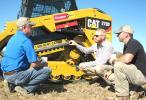 (L-R): Robert Hogue, Lumberjack Logging, New Albany, Miss.; Adam Ackerman, Caterpillar, Nashville, Tenn.; and Jason Hogue, also of Lumberjack Logging, discuss the track system on the Cat 279D compact track loader.