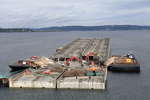 Washington State Department of Transportation photo Pontoons with superstructure are moved to a staging area on the lake so the superstructure can be demolished in place.