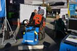 Vacuworx Design Engineer Justin Hendricks (L) and Rich Prosser, sales director, Great Lakes region, demonstrate the new SS-2 skid steer vacuum lifting system, capable of lifting more than 2,700 lbs. (1,225 kg)