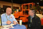 Andy Remmo (L), municipal sales manager of Power Equipment Company, discusses extended warranty options with John Hood of Epic Assurance.
