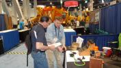 """Tom O'Brant (L) of Elgin Fastener Group speaks with Steve O'Neill of O'Neill Components about """"The Plug"""" vehicle electrical cables."""