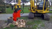A boom-mounted hydraulic tree stump grinder is attached to a mini excavator to complete the removal of a large, tree stump in a yard space. http://url.ie/11pvq