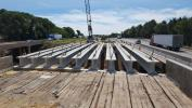 Crews install new girders for I-39/90 bridge over local roadway.