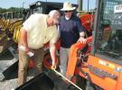Steve Albritton (L) and Bill Johns, both of Johns & Kirksey Inc., Tuscaloosa, Ala., inspect and measure the buckets on a pair of new Kubota skid steer loaders.