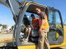 Bryan Gregor (in cab) of Gregor Well Drilling, based in Hampton Bay, N.Y., gets some operating tips on the John Deere 160G excavator from John Deere's Alex Anhalt.