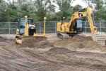 In the demo area, a Caterpillar dozer simulates setting the base layer of a road project, while a Cat excavator digs a detention basin using Trimble technology.