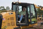Maurice Corrigan, owner of Maurice L Corrigan and Sons, Southampton, N.Y., checks out the controls of a Caterpillar dozer.