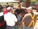 Keith Hicks (C) of QUADCO discusses his company's lineup of saw heads, mulchers and teeth with an interested group of logging professionals.
