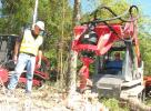 Fecon's Bob Candee (L) looks on as Neal Ashburn, Power Equipment Company forestry machine specialist, operates a Takeuchi TL10 compact track loader with a Fecon Stumpex stump grinding attachment.