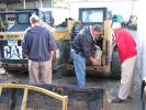 Local contractors carefully inspect a pair of Cat skid steer loaders before putting the machines on their bidding list.