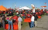 Guests visit the Kubota exhibit area featuring a lineup of construction, farming and turf management machines.