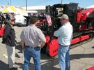 Frank Plotts (L) of Fecon, based in Lebanon, Ohio, discusses the centerpiece of the Fecon display, a Fecon FTX128L high performance prime mover.