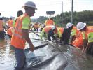 The AquaDam begins to fill while crew members keep it in position. (TxDOT photo)
