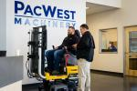 PacWest open house guest, Eric Rice, tests his skills on the Volvo excavator simulator machine with instructions from Volvo CE representative Dave Adams.