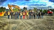 The show's cast and crew gather around the Caterpillar equipment.