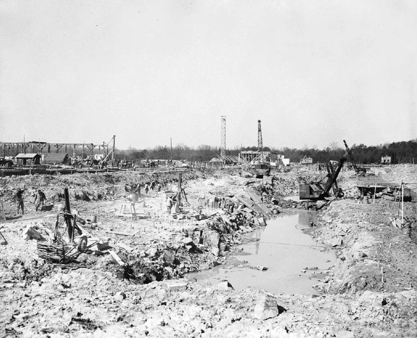 This is a view of the project site on March 21, 1938. The drills hammer the rock, which when excavated, will form the basin. The Marion shovel continues to load the Cat-Athey haulers while a Link-Belt Speeder crawler crane equipped with a clamshell bucket works in the background. (Library of Congress photo)