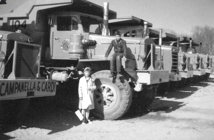Thirteen-year-old Lanny Gray sits on the only Mack LYSW three axle end dump owned by Campanella & Cardi. It is company fleet number RD104. Dressed like she may have just come from church is his young sister, Diane, standing. The end dump on the other side is a new Mack M-30X and the rest are some of the Mack LVX fleet. Lanny Gray's father was a Groton police officer and worked a security detail at the project and thus began Lanny's interest in construction and trucks.  