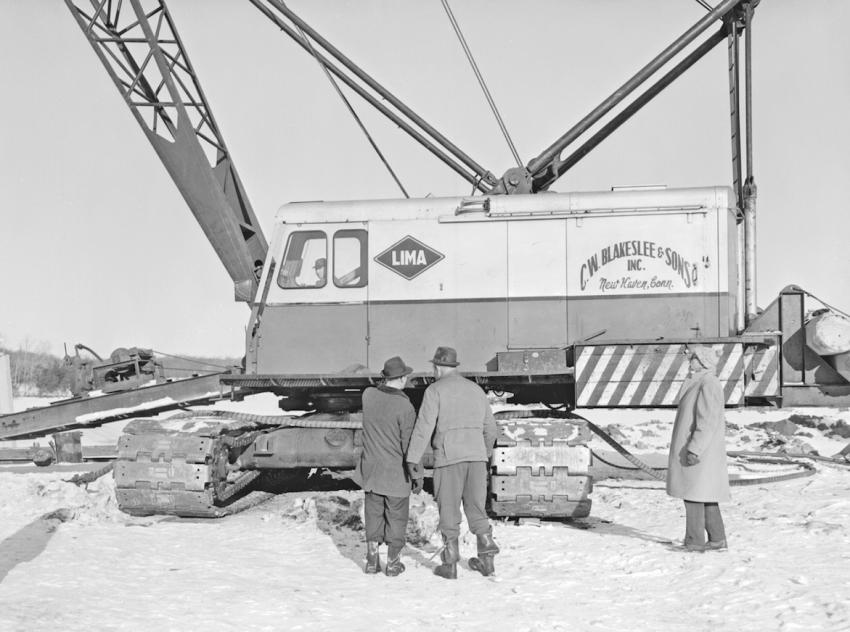 C. W. Blakeslee & Sons Inc. of New Haven, Conn., was using this Lima 1250 crawler crane to drive prestressed concrete piles for the Smith Lake Channel Bridge. Blakeslee was Campanella & Cardi's subcontractor for this work. The photo was taken Dec. 31, 1963. It appears to have been a stark winter's day heading into New Year's Eve. Blakeslee manufactured the prestressed concrete piles and bridge beams used on the project.